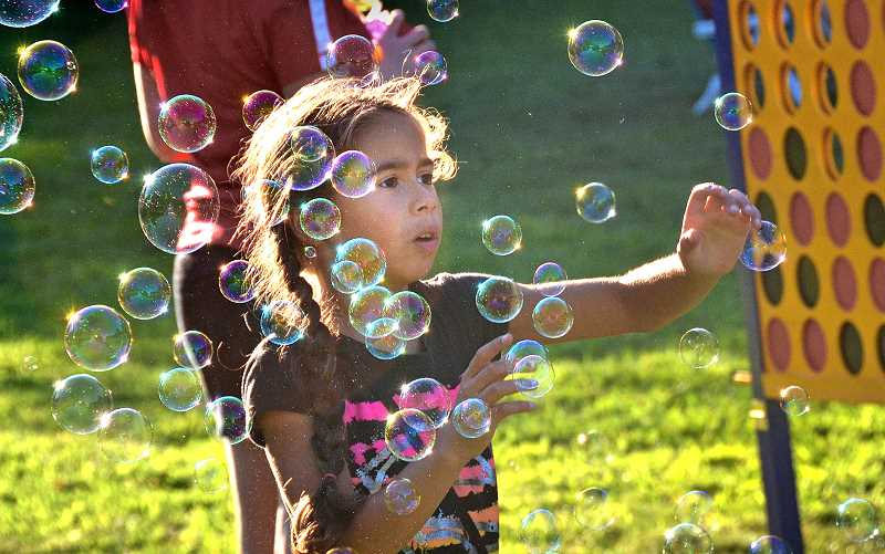 SPOKESMAN PHOTO: VERN UEYTAKE - Alix Koehler has fun with a bubble machine.