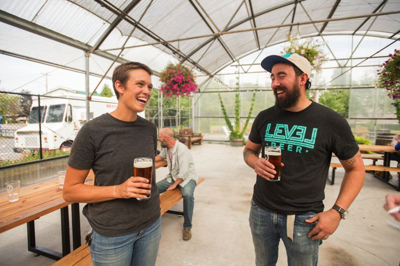 OUTLOOK PHOTO: JOSH KULLA - Level Beer employee Brindley Beckwith enjoys a laugh with co-owner Jason Barbee inside the brewery's greenhouse seating area.