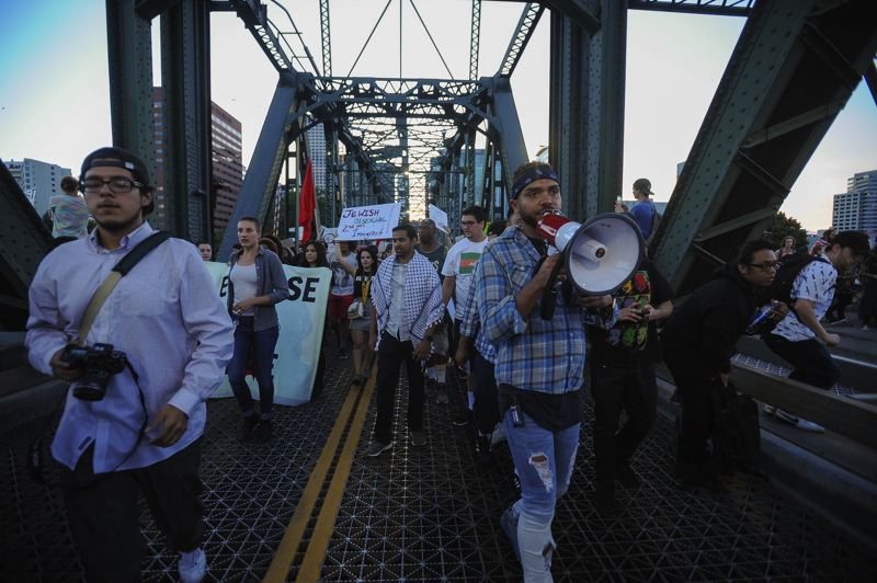 TRIBUNE PHOTO: JOSH KULLA - Gregory McKelvey, leader of Portland's Resistance (with bullhorn) leads the Eclipse Hate march across the Hawthorne Bridge Friday night. The march was held to commemorate the murder of Heather Heyer by white supremacists in Charlottesville, VA, and drew well over 1,000 people into the streets of downtown Portland.