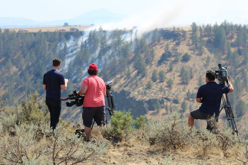 PAMPLIN MEDIA GROUP: TONY AHERN - Members of the media set up to film the still-smoking site of a plane crash near Madras Sunday. The plane crashed Saturday, Aug. 19, killing a California man.