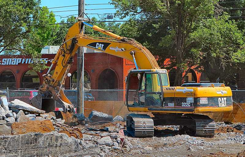 DAVID F. ASHTON - An excavator crushes the remaining corner of the Fred G. Meyer Memorial Boys & Girls Club, after asbestos abatement has been completed.