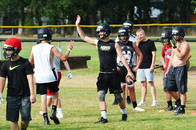 SPOTLIGHT PHOTO: JAKE MCNEAL - Chase Parkhurst, center, high-fives Liam Tindall on Aug. 14, St. Helens football's first day of practice.