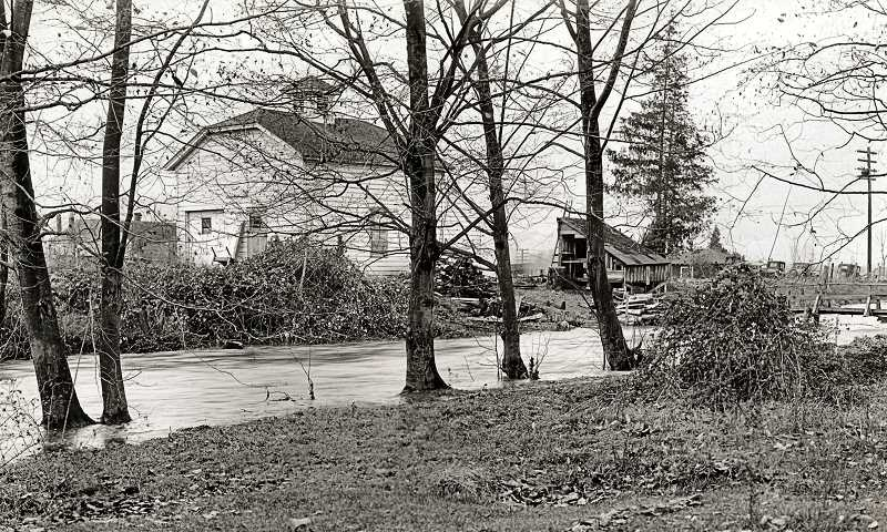 PHOTO #760, CITY OF PORTLAND ARCHIVES - A view of the south side of the milking barn of Willsburg/Wilsons Dairy, S.E. 26th and Tacoma Street. Johnson Creek is running high in the foreground. This photo was taken in 1934, two years before the barn was demolished.