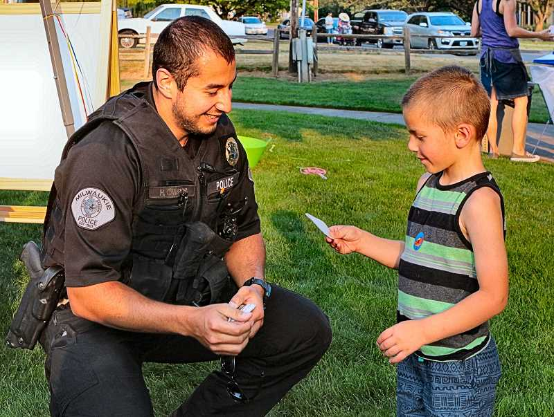 DAVID F. ASHTON - As part of the Ardenwald-Johnson Creek Neighborhood Association National Night Out celebration, Milwaukie Police Officer Hector Campos gives a sticker to Caleb Anderson.