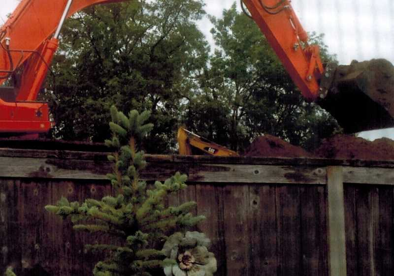 COURTESY OF RANDY AND CHERI COLLIER - During the construction of Castle Oaks East, mountains of fill were brought in, making the site as high as the Colliers' ceiling in their home below and higher than their backyard fence.