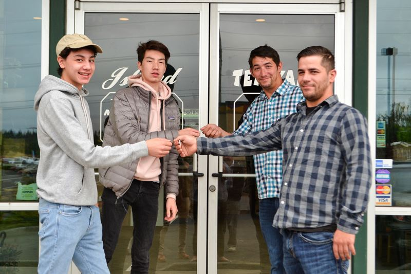 POST PHOTO: BRITTANY ALLEN - Michael and Keegan Ryan hand over the keys to their late father's restaurant, Island Teriyaki, to David and Carl Kidd.