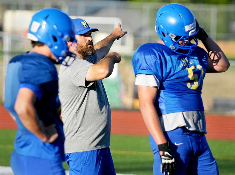 SETH GORDON - First-year Newberg coach Kevin Hastin works with offensive lineman during practice last week. Hastin and the Tigers will participate in a jamboree at West Salem Friday before hosting Barlow Sept. 1 in the season opener.