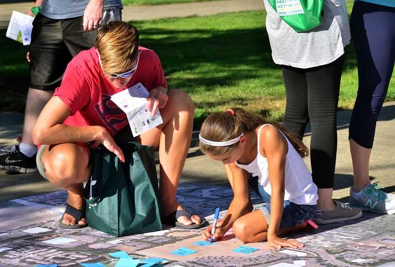 SPOKESMAN PHOTO: VERN UYETAKE - Joey, left, and Alix Koehler add their suggestions to the Town Center big map.