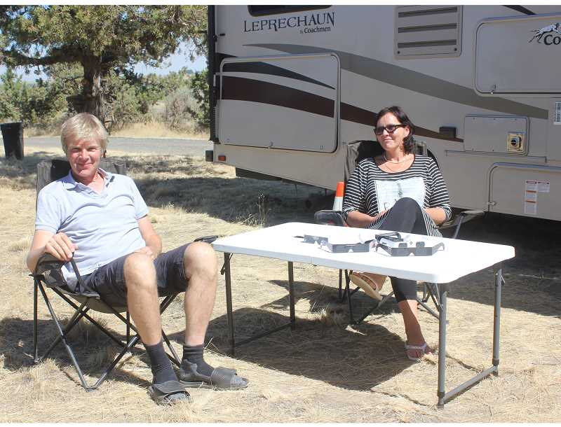 SUSAN MATHENY/MADRAS PIONEER - Aart Beenken and Remigija Poceieme, from the Netherlands, relax at the Madras campsite they discovered through a visit to Art Adventure Gallery. On the table are solar viewing glasses from Aart Beenken's many solar eclipse trips.