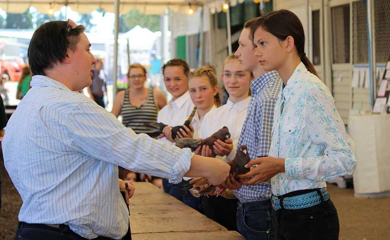 TIDINGS PHOTO: SAM STITES - Carly Shanklin (left) took home grand champion in the 4-H pigeon showmanship competition at the Clackamas County Fair. Shanklin also competes in public speaking, and submits artwork to the exhibit hall.