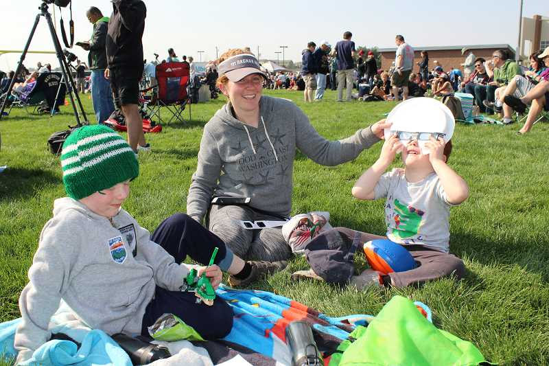 HOLLY M. GILL - Hilary Rasmussen, of Seattle, Washington, helps her sons, Luke, 5, and Stephen, 3, watch the eclipse on Aug. 21, in the Madras High School stadium.