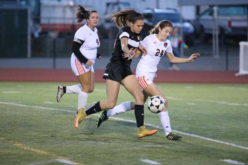 PIONEER FILE PHOTO - Molalla junior Mattie Myers (middle) fights for the ball against a Gladstone defender last season.