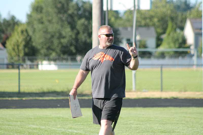 PIONEER PHOTO: CONNER WILLIAMS - Molalla football's head coach Tim Baker gives calls to the offense during a 7-on-7 passing league scrimmage last month at Woodburn High School.