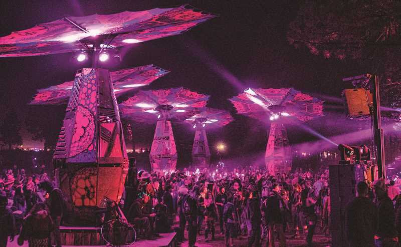 LON AUSTIN - Music lovers fill the area in front of the moon stage as a DJ and light show play late Thursday night.