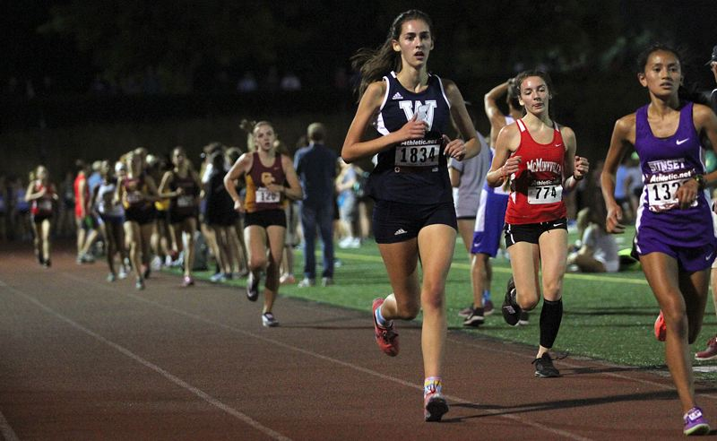 PAMPLIN MEDIA GROUP PHOTO: MILES VANCE - Wilsonville's Kate Stewart runs down the back stretch during the junior 3,000-meter race at the Wilsonville Night Meet on Friday.