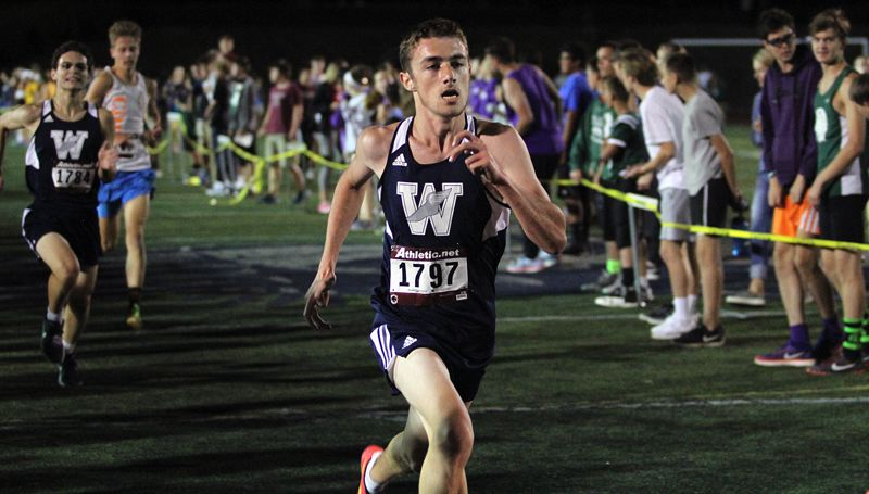 PAMPLIN MEDIA GROUP PHOTO: MILES VANCE - Wilsonville's Nicholas Whitaker races home to finish sixth in the senior 3,000-meter race at the Wilsonville Night Meet on Friday.