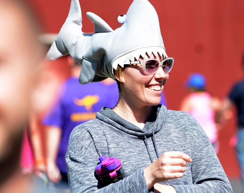 OUTLOOK PHOTO: DAVID BALL - Alex Lewis from Grand Rapids, Mich., sports a shark hat on her head while waiting at the Main City Park exchange point with her Sharknado teammates.