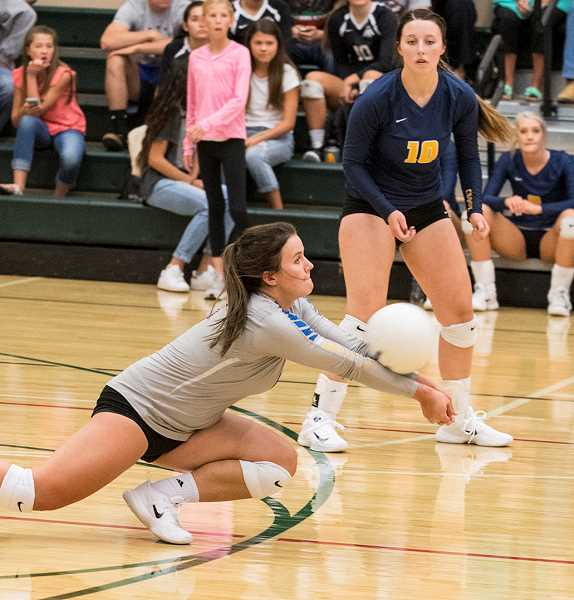 LON AUSTIN/CENTRAL OREGONIAN - Mekynzie Wells digs a ball during the Cowgirls set against Bend. Wells led the Cowgirls in digs during the jamboree with 18. Kerigan Waibel is in the background.