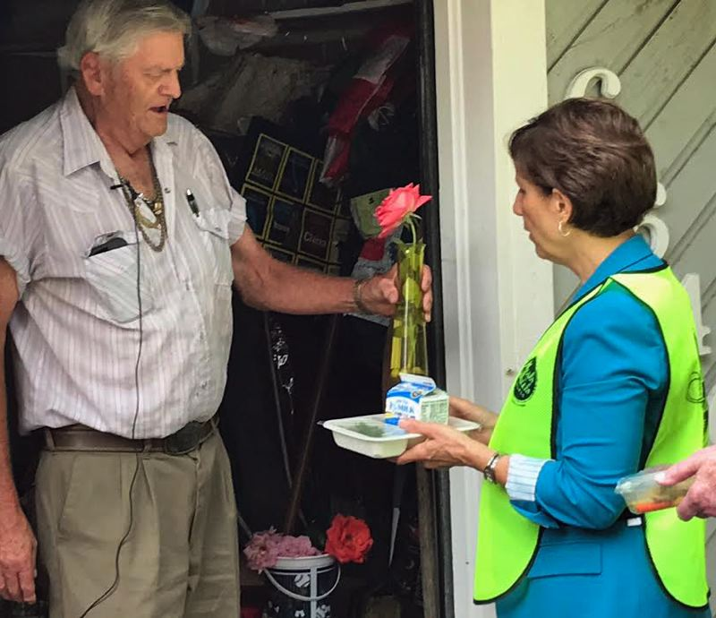 TIMES PHOTO: DANA HAYNES - Congresswoman Suzanne Bonamici delivers a meal to Vietnam vet Larry Johnson of Beaverton; he, in return, offered her a flower from his garden.