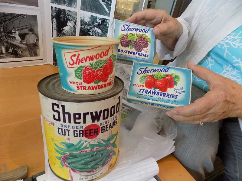 GAZETTE PHOTO: RAY PITZ - Yvonne Scheller shows several packages (and cans) containing the Sherwood label, which were packaged during the heydey of the Portland Canning Company.