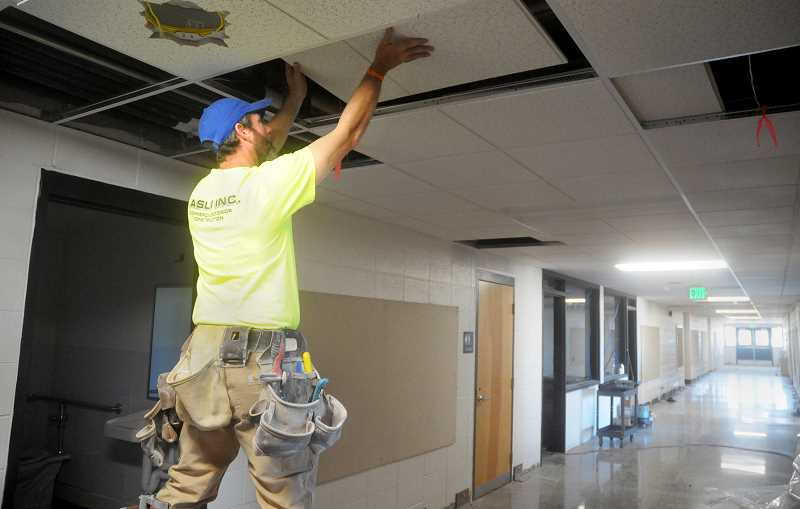 SETH GORDON - Tim Tinkham of subcontractorCaslin Inc. installs ceiling tiles in the main hallway of St. Paul Elementary School last week. Construction crews are pushingto complete the $2.9 million renovation before classes begin Sept. 5.