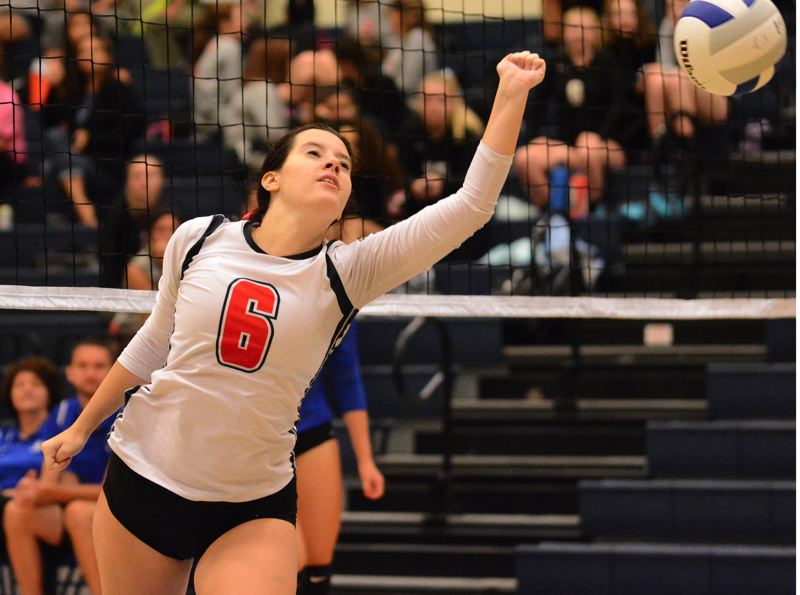 OUTLOOK PHOTO: DAVID BALL - Corbetts Ruby Robison reaches out a hand to deflect a Valley Catholic kill.