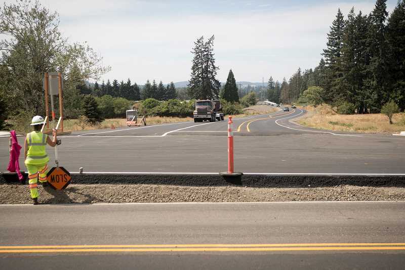 PAMPLIN MEDIA GROUP PHOTO: JAIME VALDEZ - A flagger directs traffic in front of Basalt Creek Parkway shortly after the new road opened to traffic. Basalt Creek Parkway serves as an alternate route for traffic while Tonquin Road is closed. Once both roads are open, transportation planners hope traffic flow through the area will improve.