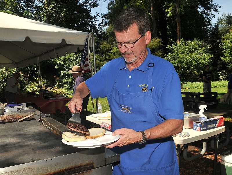 TIDINGS PHOTOS: VERN UYETAKE - Tom Laun prepares a Lion Burger at a recent barbeque held at the McLean House.