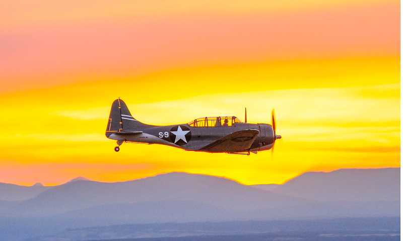 TOM BROWN - The SBD Dauntless, flown by Brent Connor, is one of several World War II-era airplanes that are part of the Erickson Aircraft Collection, that were part of the 2017 Airshow of the Cascades, Aug. 25-26, at the Madras Municipal Airport. Connor pilots the aircraft during a brilliant sunset Friday night.