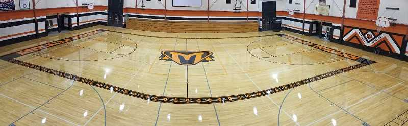COURTESY PHOTO - After grinding the high school gym floor down to bare wood, here is a view of the completed project with the new logo.