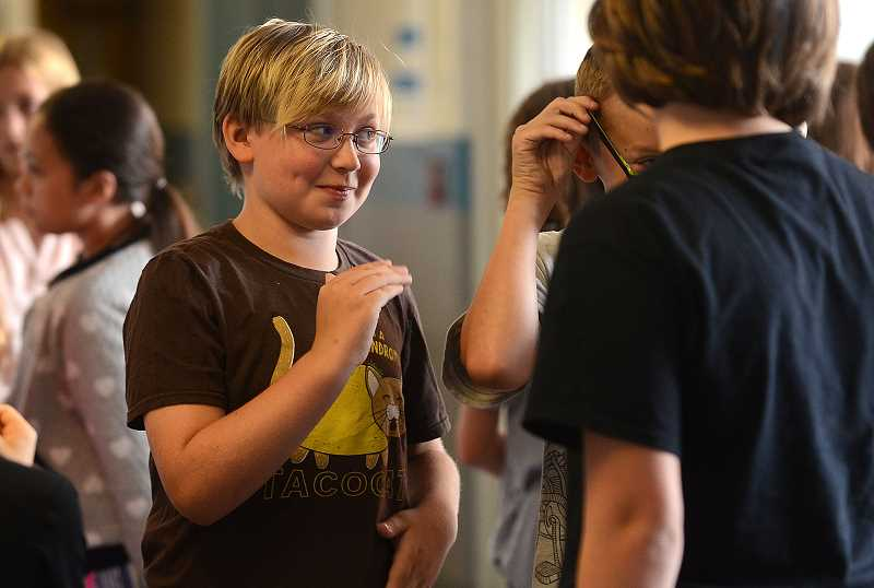 REVIEW PHOTO: VERN UYETAKE - Max Harrell of Lakeridge Junior High chats with a fellow student Tuesday during an ice-breaker activity on the first day of school.