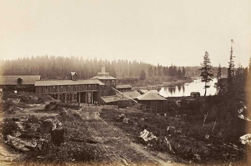 SUBMITTED PHOTO: LAKE OSWEGO PRESERVATION SOCIETY - This photo taken by famed 19th century landscape photographer Carleton Watkins shows the site of the Oregon Iron Company's facilities just a couple of months after the furnace went into blast operation in 1867. Sucker Creek (Oswego Creek) is on the right, and the Willamette River can be seen in the background. The blast furnace is in the tall building in the center with the chimney.