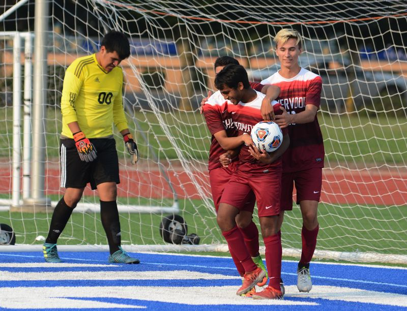 PAMPLIN MEDIA GROUP: DAVID BALL - Sherwood's Danny Dhas celebrates with his teammates after scoring a goal in Tuesday's game at Gresham.