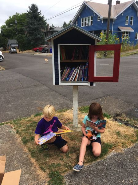 SUBMITTED PHOTO - Jonathan W. Alwine and Amanda Dexter Alwine check out the new free library at the corner of 11th Street and Jefferson Street in Oregon City.