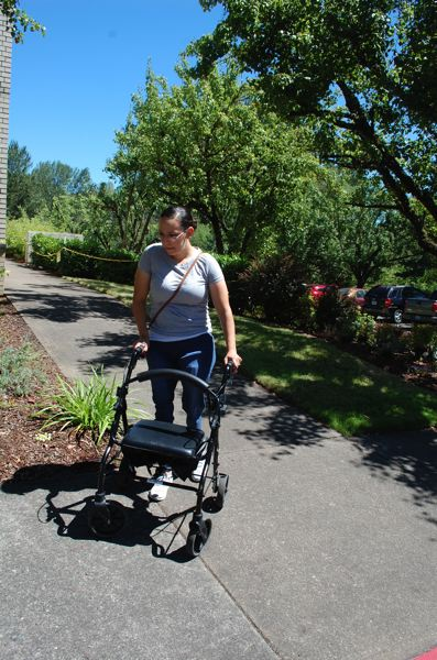 PHOTO BY: RAYMOND RENDLEMAN - Kelsey Zionskowski, 28, maneuvers around a corner with her walker.