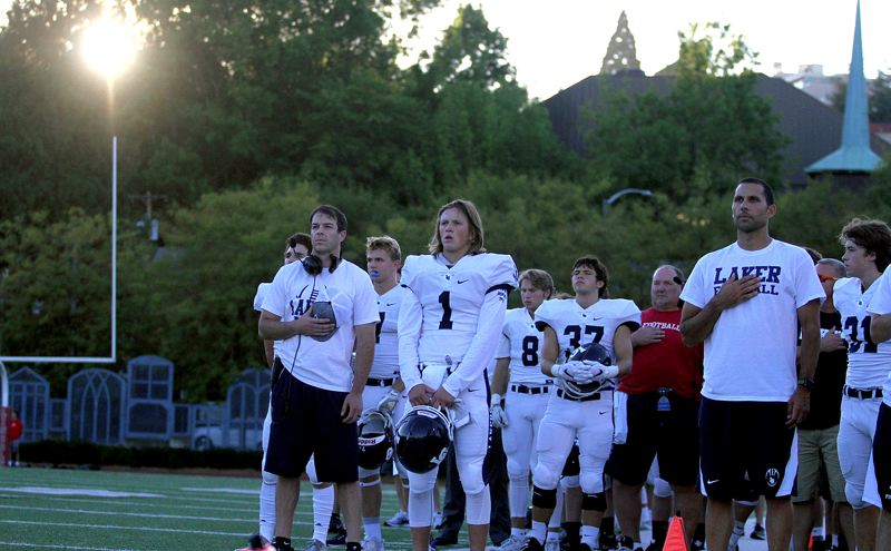 REVIEW PHOTO: MILES VANCE - The Lake Oswego football team stands for the national anthem before the beginning of their 40-0 win at Lincoln High School in non-league play Friday night.