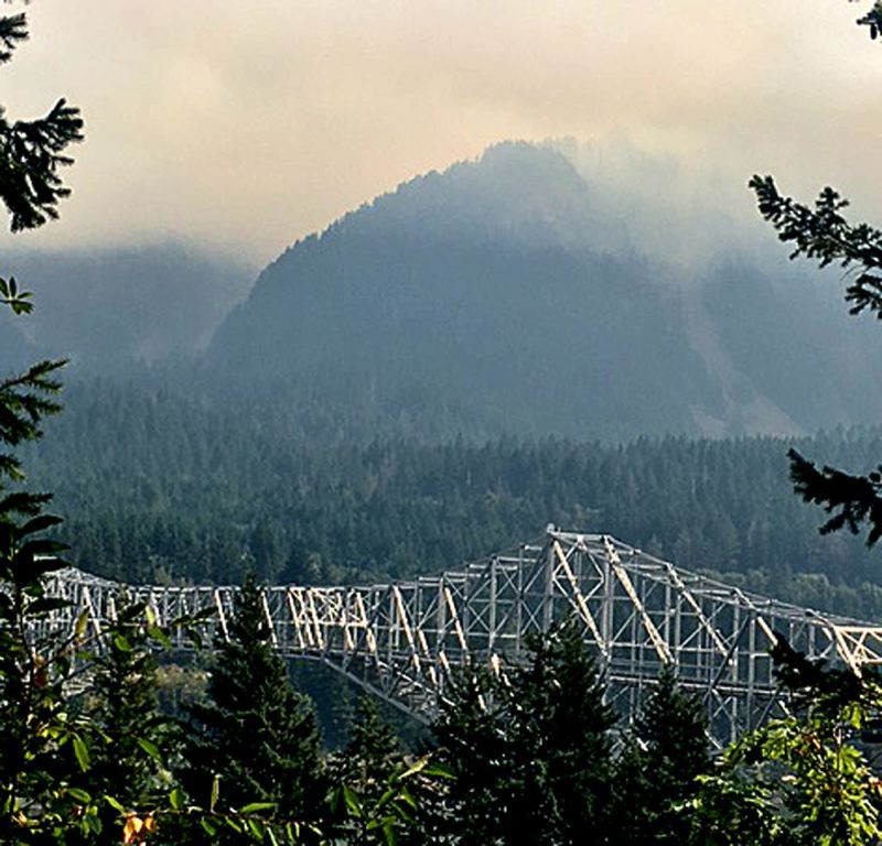 PAMPLIN MEDIA GROUP: JOHN SCHRAG - Smoke clung to the hills around the Bridge of the Gods near Cascade Locks during the weekend as the Eagle Creek Fire burned thousands of acres in the Columbia River Gorge. More smoke reached the Willamette Valley on Tuesday, as the wind shifts from the east.