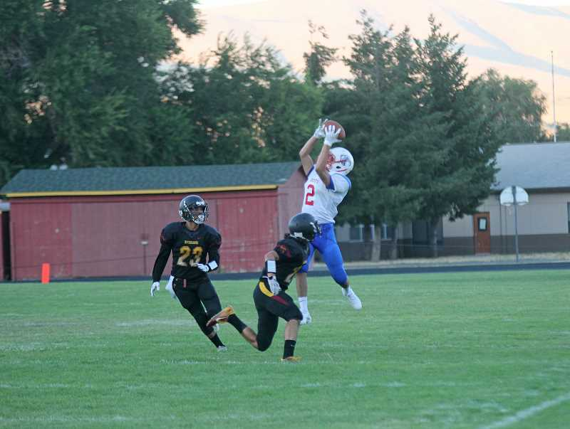 WILL DENNER/MADRAS PIONEER - Madras senior Robert Pachecho (2) led the Buffs in receiving, linking up with quarterback Liam White for 54 yards on three catches.