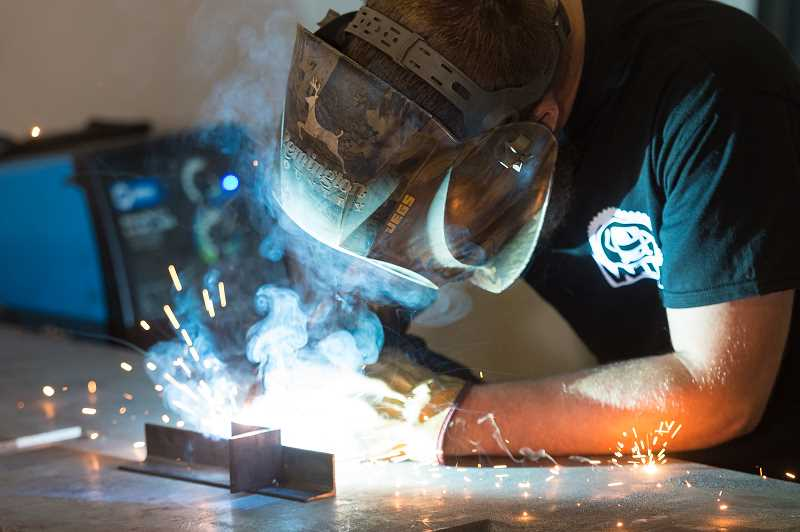 NEWS-TIMES PHOTO: CHRISTOPHER OERTELL - Brady Sheets welds some metal at Western Iron Works, his new shop in Gaston.