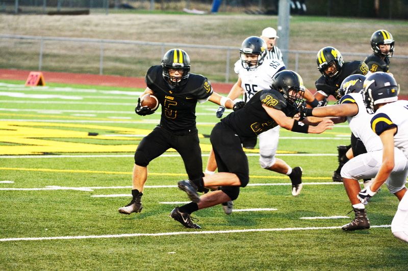 SPOTLIGHT PHOTO: JAKE MCNEAL - Junior running back Shawn Lee (5), senior tight end Zane Weis (32) and the Lions will try to beat Scappoose for the second year in a row.