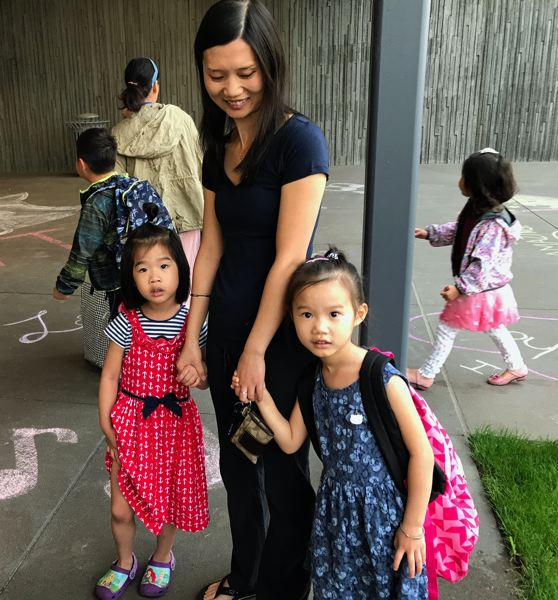 TIMES PHOTO: DANA HAYNES - With their backpacks and new dresses, Ivy Zhang, left, and Iris Zhang, both 6, are ready for school. They came Tuesday with their mom, Isabella Zhang.