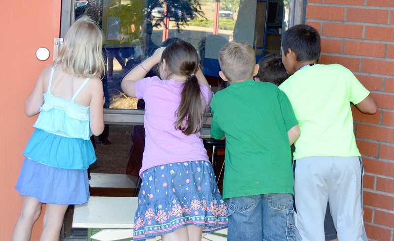 PIONEER PHOTO: CINDY FAMA - The school doors of Colton Elementary School can't open soon enough as these kids peek through the window of their new classroom.