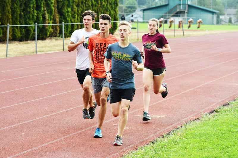 SPOTLIGHT PHOTO: JAKE MCNEAL - Indians senior Linnaea Kavulich, right, pictured with, from left, senior Josiah Oliver, sophomore Isaiah Ebert and senior Caleb Peckover in practice at Scappoose High School, won the varsity girls' Class 1A-4A 5,000-meter run at the Ultimook Race Nike Invitational in 20 minutes, 30.35 seconds on Saturday, Sept. 2, at Hydrangea Ranch in Tillamook.
