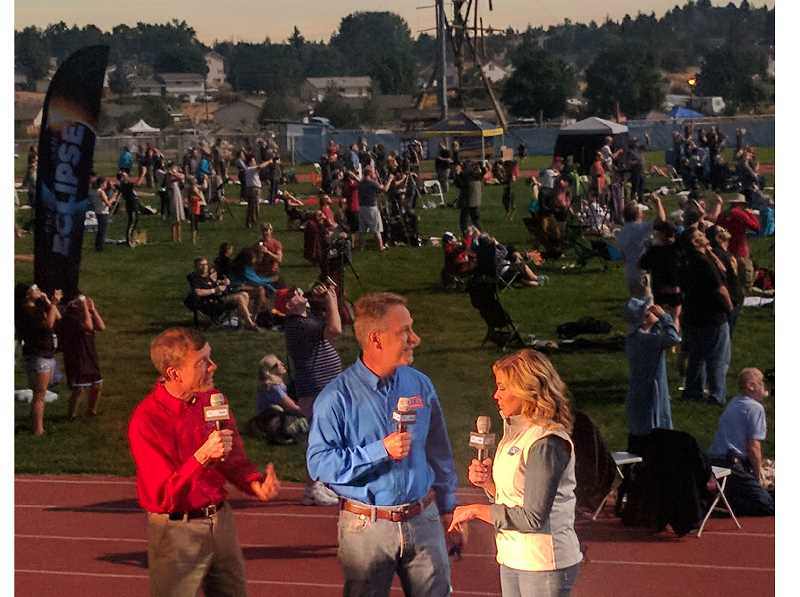 PHOTO BY STEPHANIE VAN BELLE - From left, Jeffrey Hall, director of Lowell Observatory in Flagstaff, Arizona, astronomer Gerard VanBelle, of Lowell Observatory, and Laura Sivan, of the Science Channel, do a live interview from the Madras High School football fiedl during the total eclipse.
