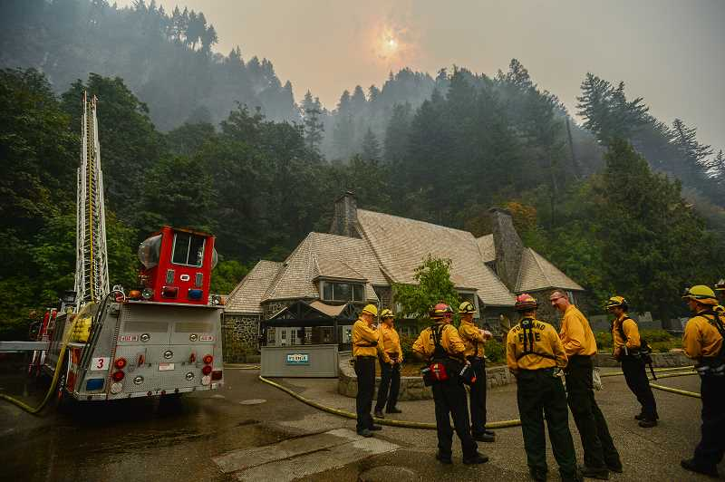PAMPLIN MEDIA GROUP: JOSH KULLA - Portland Fire and Rescue personnel relax for a moment Wednesday as they battle the ongoing Eagle Creek Fire, which increased to an estimated 31,000 acres in size as of Wednesday morning. The historic Multnomah Falls Lodge, however, was subject to intense firefighting efforts that were successful as the fire swept west toward Crown Point. Officials warn, however, that the fire is still zero percent contained.