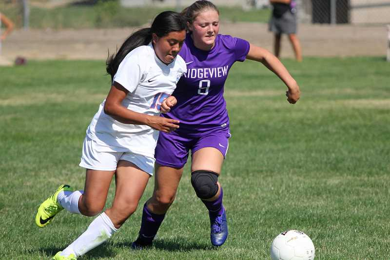 WILL DENNER/MADRAS PIONEER - Madras forward Jackie Zamora (left) played an active role in the Buffs' attack against Ridgeview during the first half, before she suffered an ankle injury colliding with an opponent and had to be helped off the field.