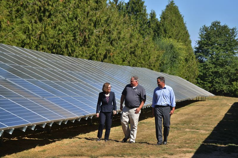 COURTESY NORTHWEST HAZELNUT COMPANY - Gov. Kate Brown checks out the new solar array with her former Senate colleague Larry George, middle, who co-owns Northwest Hazelnut Co. with his brother, Shaun George, right. It's the nation's largest filbert processor, and going solar should help it win more deals with big agricultural companies.