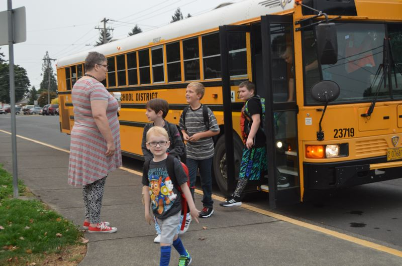 SPOTLIGHT PHOTO: NICOLE THILL - Columbia City Elementary School students are welcomed by staff as they get off the bus Tuesday morning, Sept. 5. Elementary school students in the St. Helens School District went back to school Tuesday, and, for the first time since 2012, Columbia City Elementary School opened its door to students.