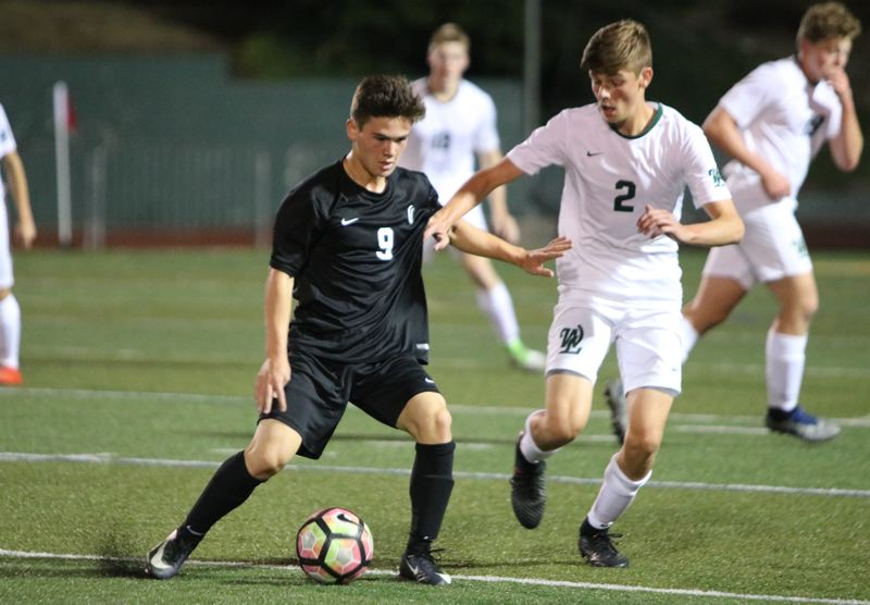 REVIEW/NEWS PHOTO: JIM BESEDA - Clackamas' Keanu Cano (9) controls the ball under pressure from West Linn's Ben Walker (2) during Thursday's non-conference boys' soccer match at West Linn High School.