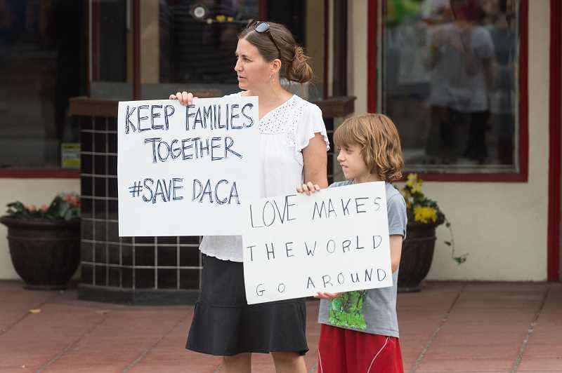 NEWS-TIMES PHOTO: CHRISTOPHER OERTELL - Brenda Zook Friesen and her son Michael, 10, both from Forest Grove, hold signs in support during a DACA rally.